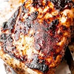 above shot of a grilled pork loin held by silver tongs