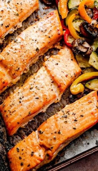 roasted maple teriyaki salmon fillets on a baking sheet with roasted veggies