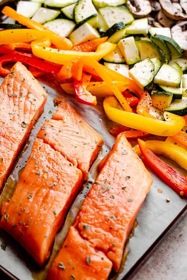raw salmon fillets on a baking sheet with vegetables
