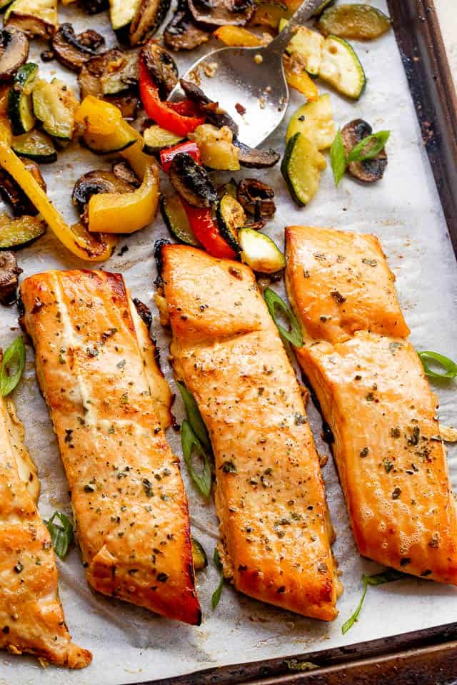 roasted maple teriyaki salmon fillets on a baking sheet with roasted veggies