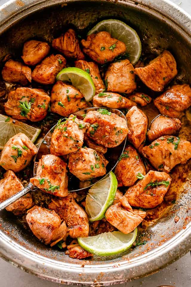 skillet filled with chicken pieces tossed with taco seasoning and pan seared