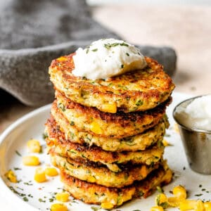 stack of zucchini corn fritters set on a white plate with yogurt dip next to it, and a gray linen napkin behind the plate