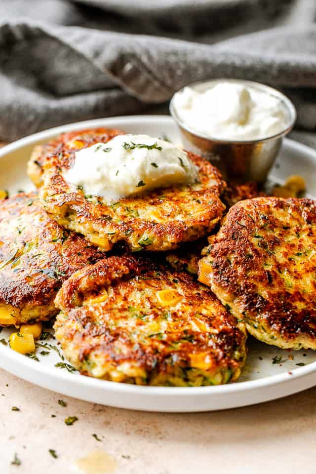 close up side shot of arranged corn zucchini fritters on a plate and topped with a dollop of yogurt dip
