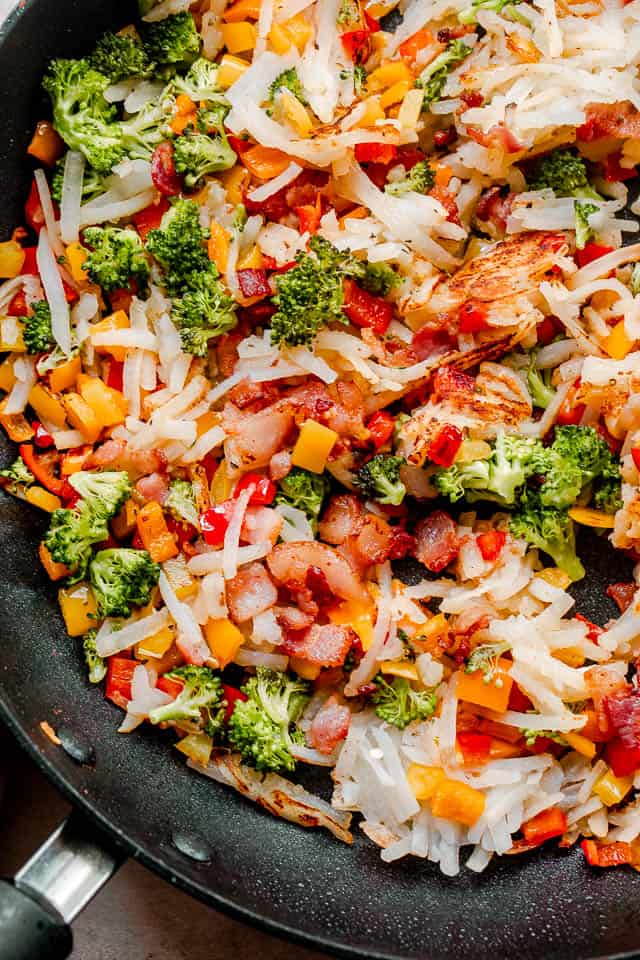 black skillet filled with hashbrowns, diced bell peppers, and small broccoli florets