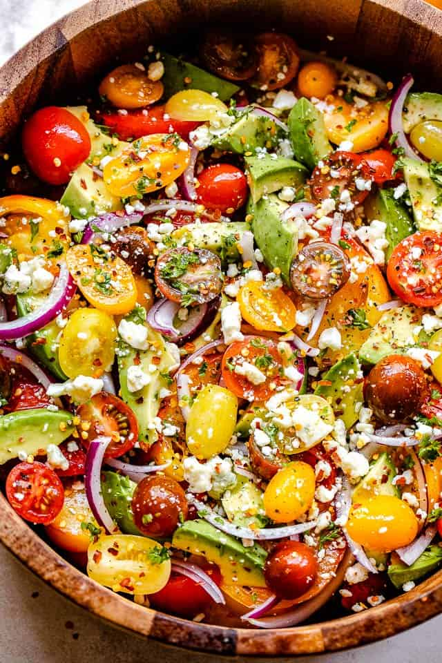 chopped tomatoes, avocados, onions, and cheese in a wooden salad bowl