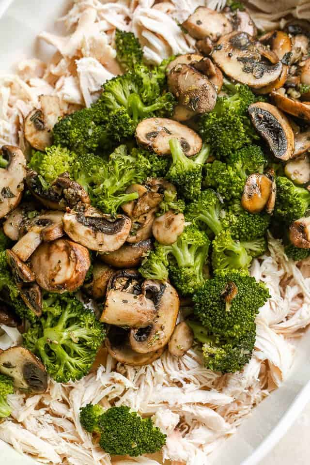 cooked broccoli and mushrooms set over shredded cooked chicken