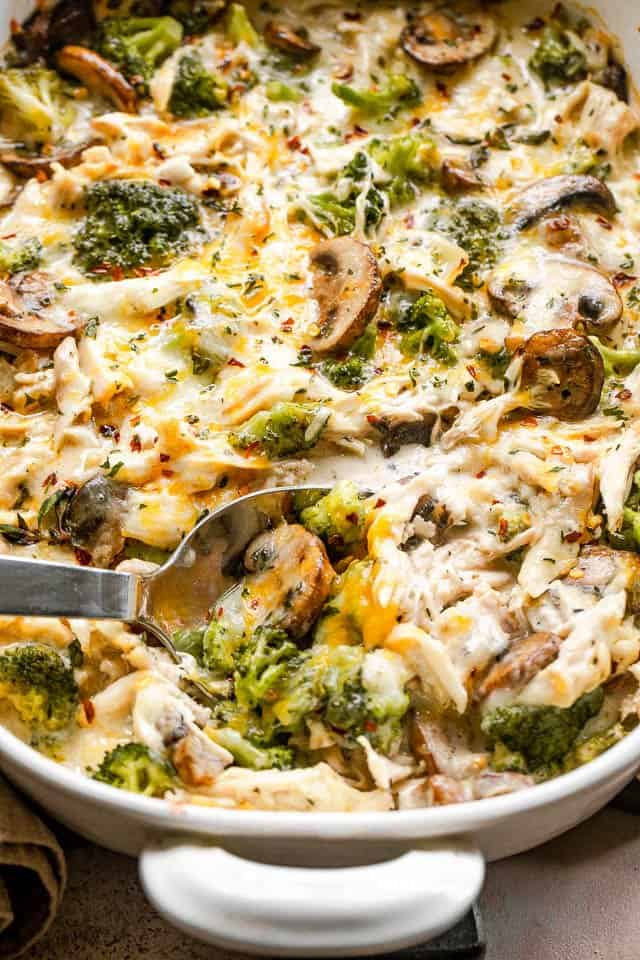 serving spoon scooping out chicken casserole from a white baking dish