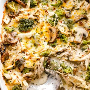 overhead shot of chicken broccoli casserole with a serving spoon inside the baking dish
