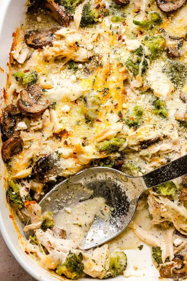 overhead close up shot of chicken broccoli casserole with a serving spoon inside the baking dish