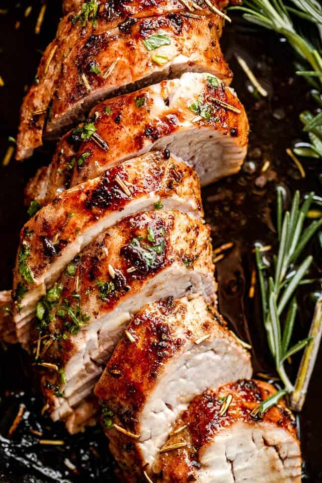 top view of slices of pork tenderloin on a dark background with rosemary branch next to it