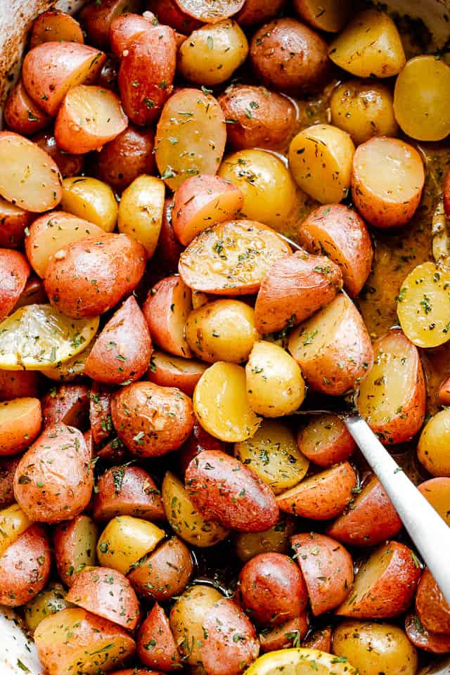 overhead shot of halved yellow and red small potatoes in a baking dish