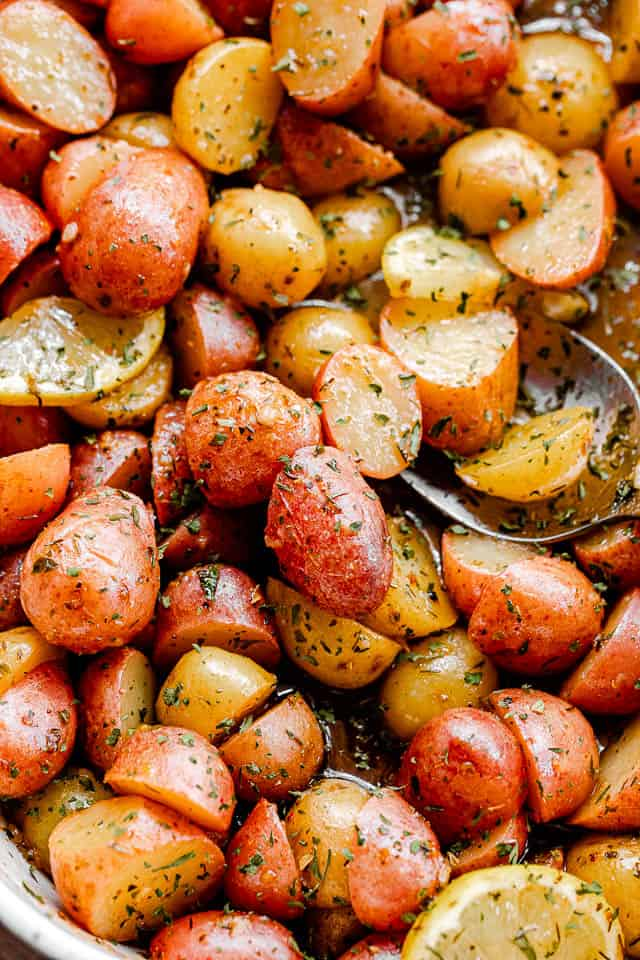 overhead shot of marinated halved yellow and red small potatoes in a baking dish
