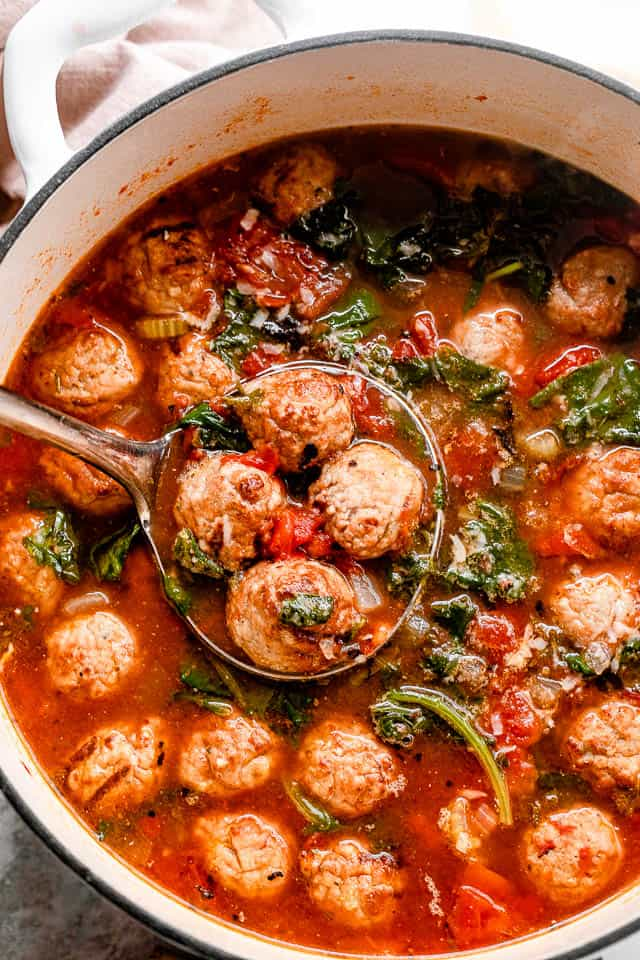 a pot of meatball soup with a ladle scooping out 4 meatballs