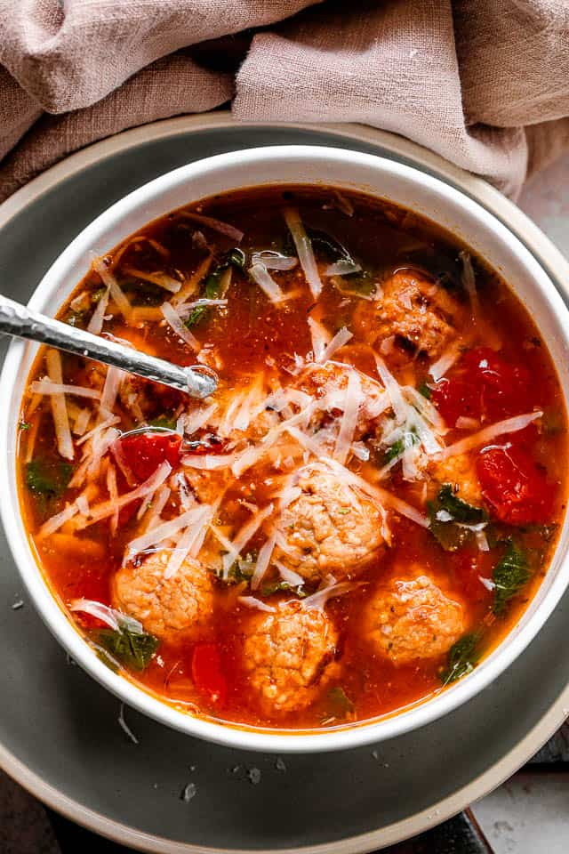 parmesan cheese garnished meatball soup in a white soup bowl