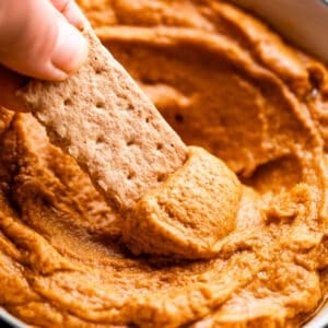 side shot of scooping out pumpkin peanut butter dip with a graham cracker