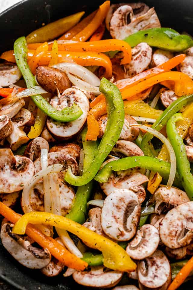 colored bell peppers cut in strips and cooked in a black skillet with mushrooms and onions