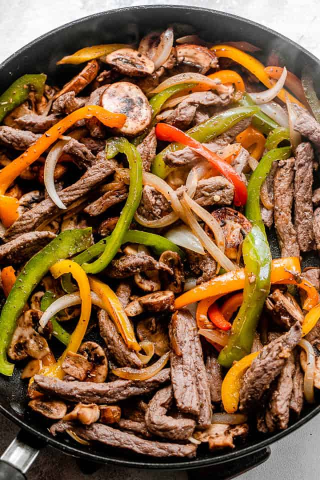 cooking strips of steak, mushrooms, and bell peppers in a black skillet