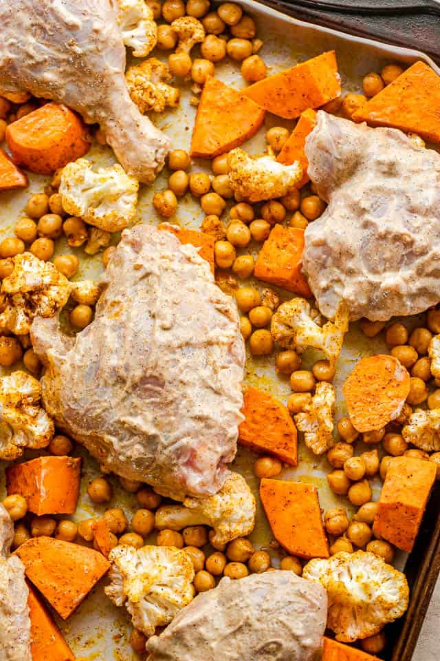 overhead shot of a sheet pan with yogurt marinated chicken pieces set on top of uncooked sweet potato cubes, cauliflower florets, and garbanzo beans