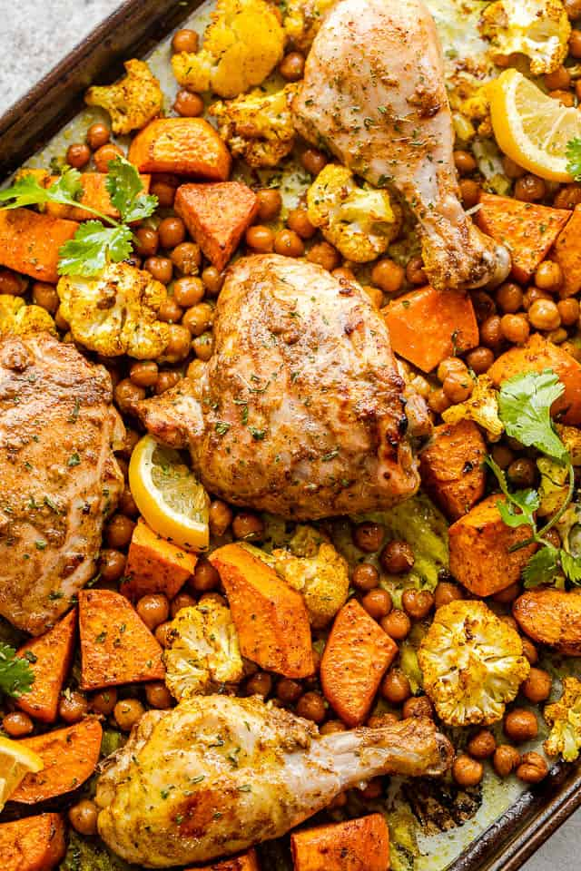 sheet pan with cooked chicken thighs, drumsticks, sweet potatoes, cauliflower florets, and chickpeas