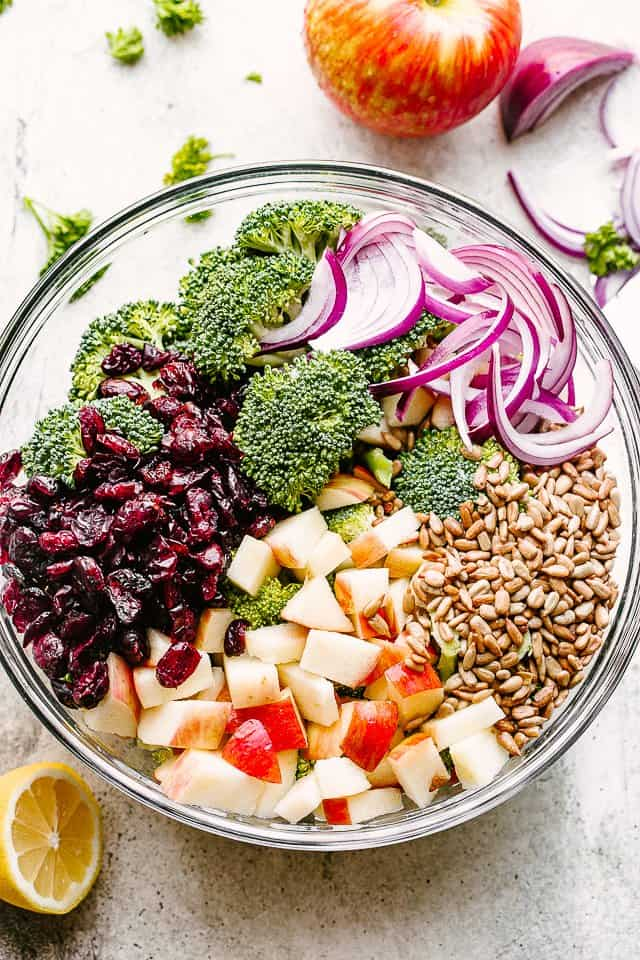 overhead shot of a salad bowl with arranged broccoli, nuts, cranberries, apples, and red onions.