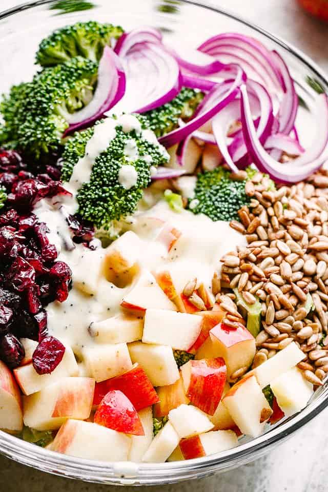 overhead shot of a salad bowl with broccoli, nuts, cranberries, apples, red onions, and salad dressing