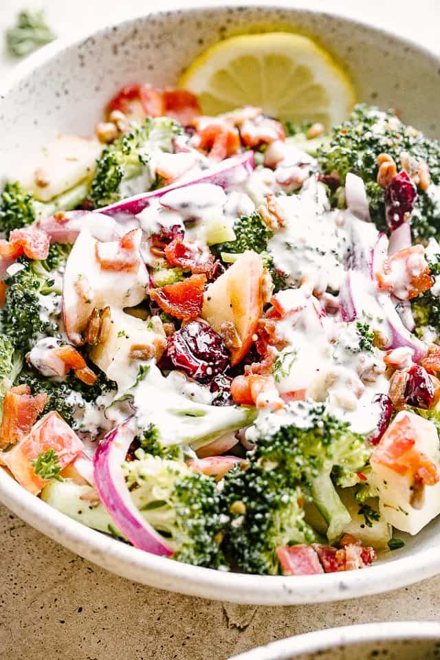 apple broccoli salad in a salad bowl and topped with poppyseed dressing