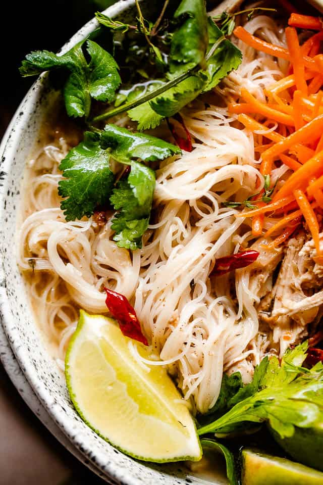 close up overhead shot of instant pot chicken pho in a bowl garnished with carrots, cilantro, and lime wedges