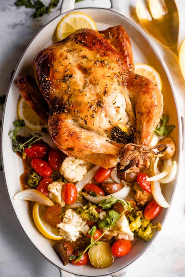 overhead shot of a whole roast chicken served on an oval plate with variety of vegetables