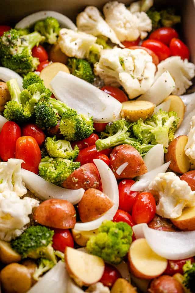 close up shot of chopped up broccoli, onions, cherry tomatoes, potatoes, and cauliflower