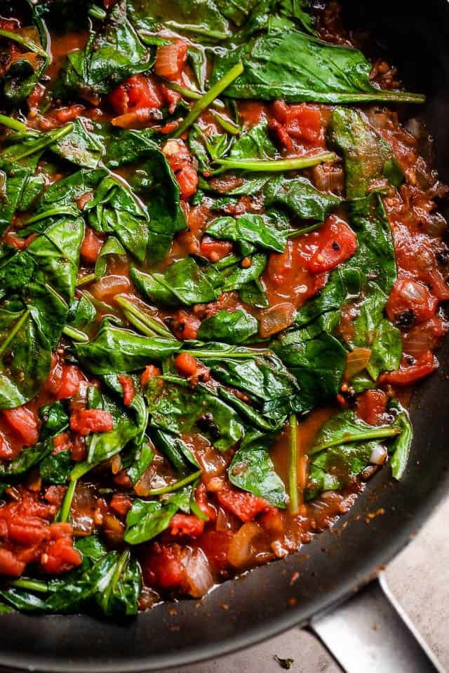 skillet with tomato sauce with spinach