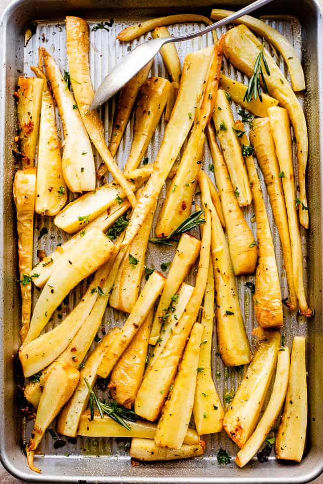 overhead shot of a baking sheet with roasted parsnips