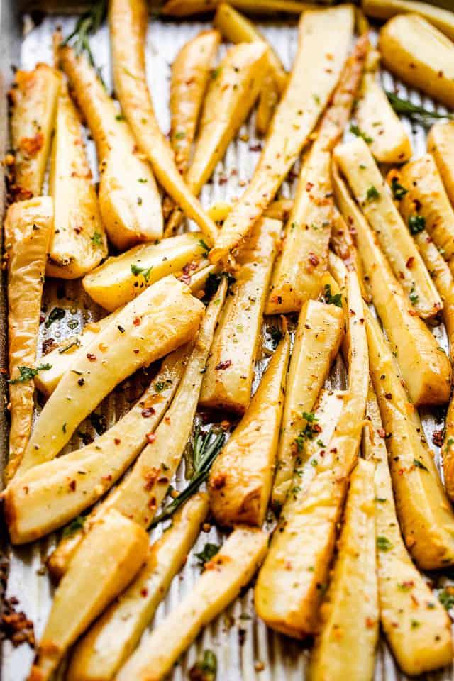 side shot of roasted parsnips on a silver baking sheet