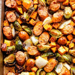 overhead shot of a sheet pan with cooked andouille sausage, brussels sprouts, and sweet potatoes