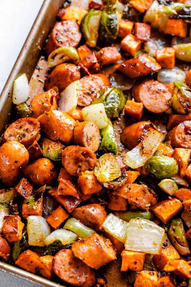 picture of a baking pan with cooked andouille sausage, brussels sprouts, and sweet potatoes