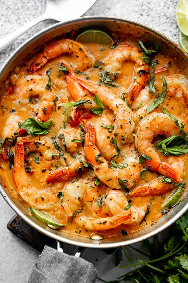 wide overhead shot of shrimp in a skillet with coconut sauce