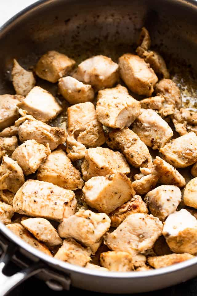 diced chicken cooking in a stainless steel skillet