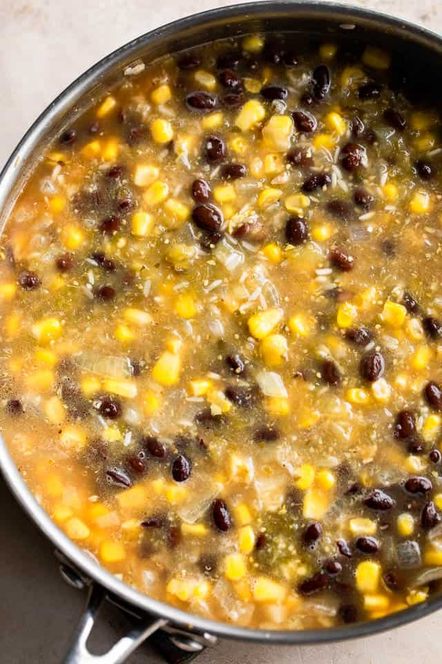 black beans and corn in a skillet with salsa verde sauce