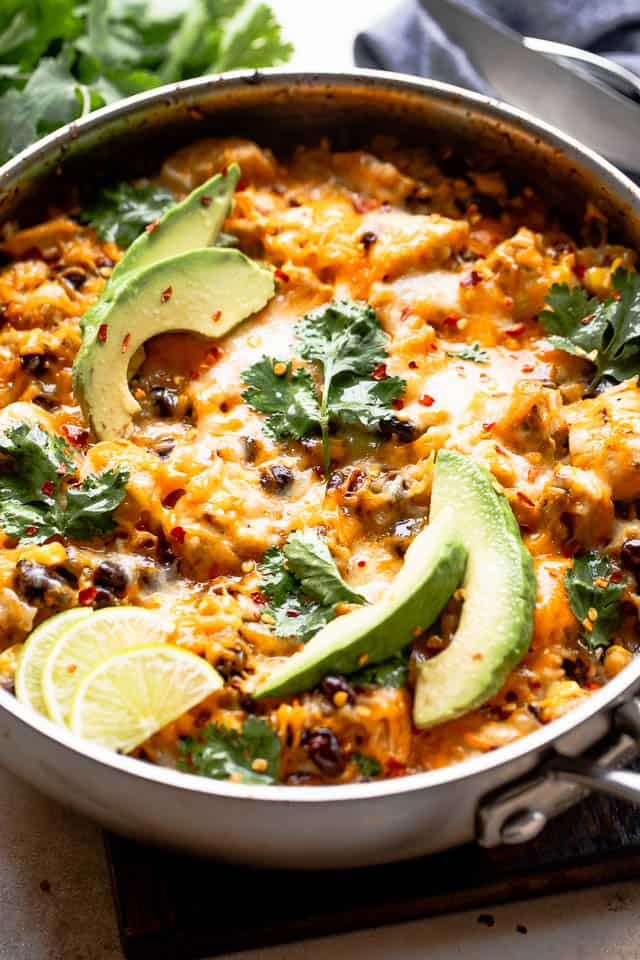 side shot of a skillet with salsa verde chicken and rice casserole garnished with avocado, limes, and cilantro