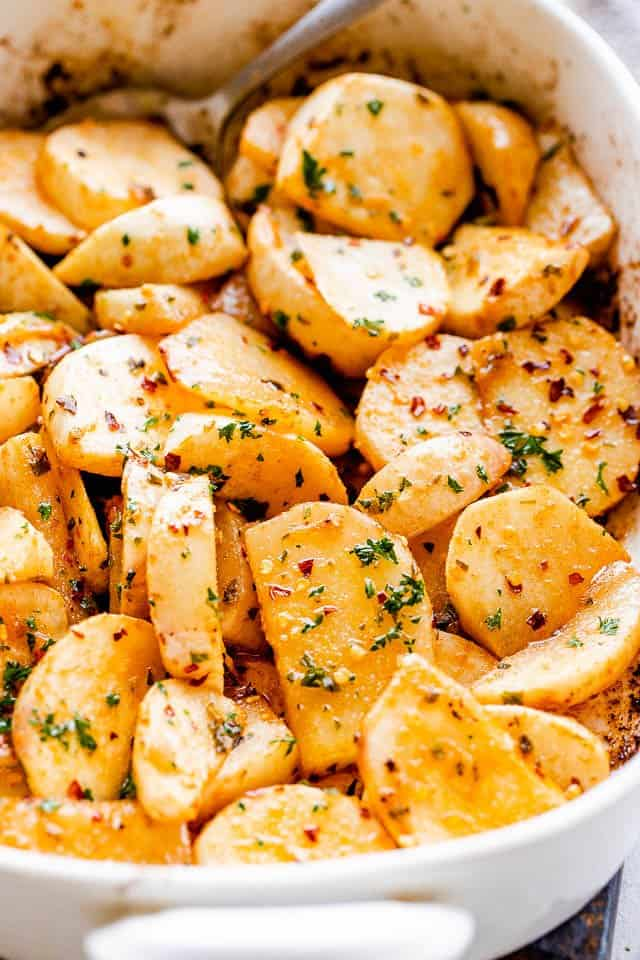 side shot of a baking dish with roasted turnips topped with herbs and pepper flakes