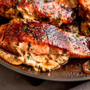 side shot of creamy stuffed cajun salmon fillets in a skillet