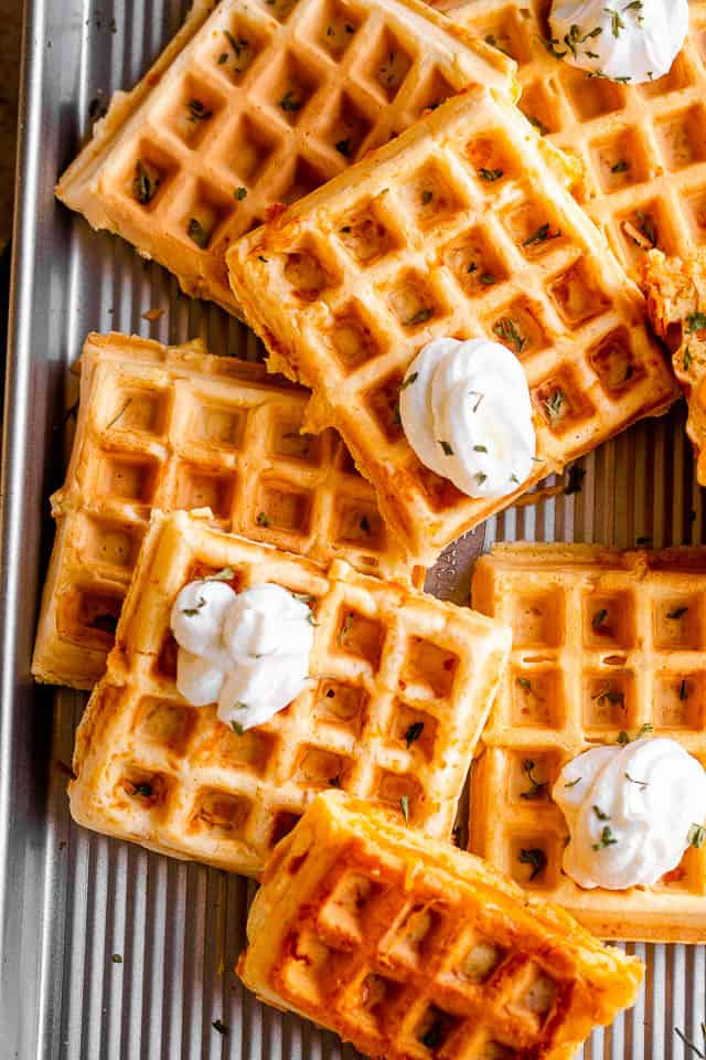 overhead shot of a number of chaffles placed on a baking sheet and topped with dollops of sour cream