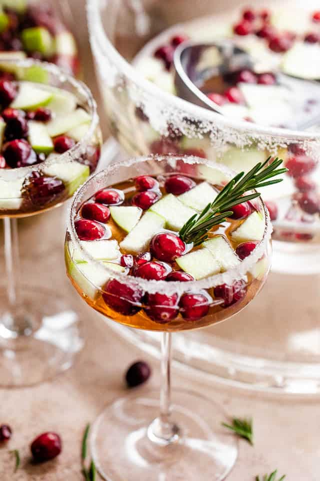 Christmas Mimosas served in champagne coupe glasses garnished with cranberries, apples, and rosemary sprigs