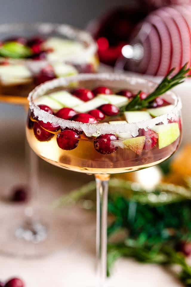 up close shot of two coupe glasses filled with prosecco and garnished with fresh cranberries, apples, and rosemary sprigs