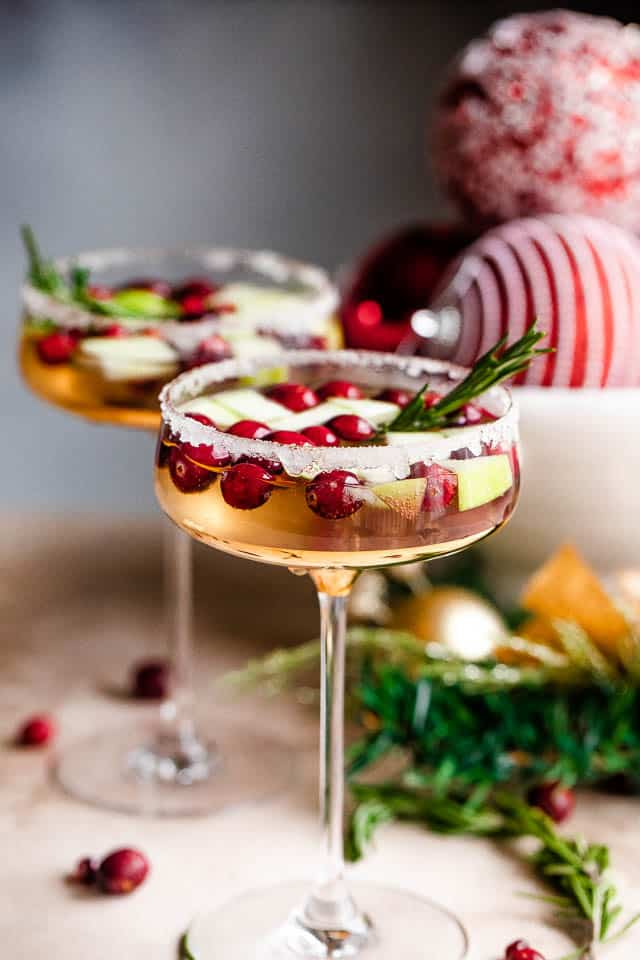 wide shot of two coupe glasses filled with prosecco and garnished with fresh cranberries, apples, and rosemary sprigs