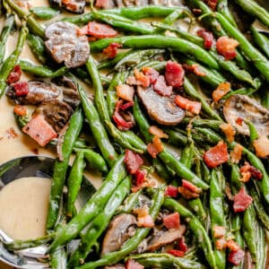 green beans and mushrooms cooking in a creamy parmesan sauce and topped with diced bacon
