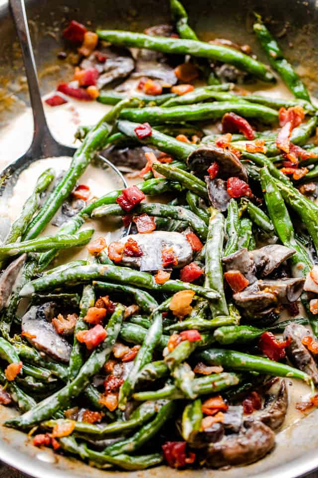 side shot of cooked green beans and mushrooms topped with bacon