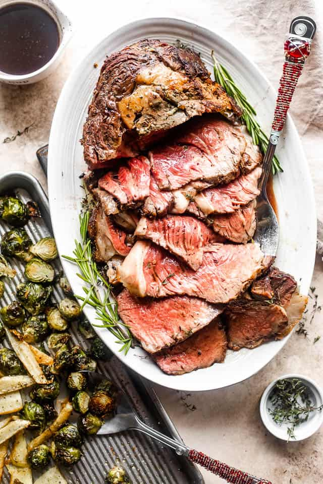 overhead shot of boneless prime rib cut in slices and served on a platter with large fork