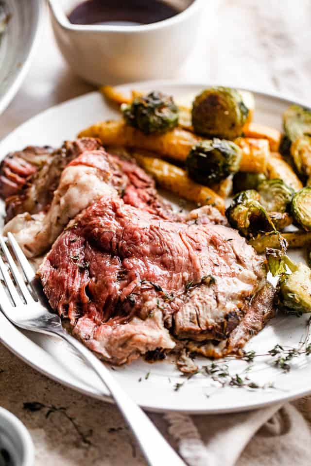 dinner plate with a slice of prime rib, roasted brussel sprouts, and parsnips