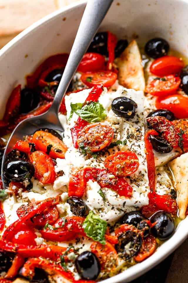 side shot of a baking dish with baked feta cheese, tomatoes, olives, and red peppers
