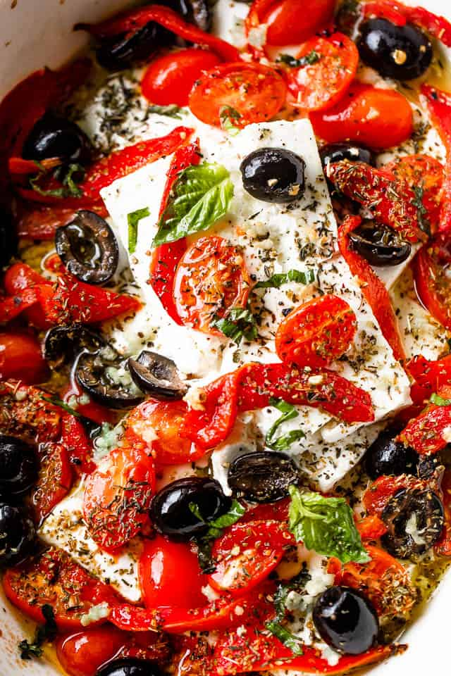 overhead close up shot of baked feta cheese blocks topped with tomatoes, olives, peppers, and herbs